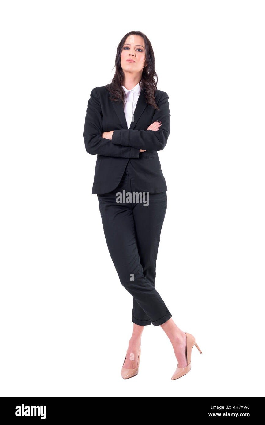 Confident business woman in black suit with crossed arms and crossed legs standing. Full body isolated on white background. - Stock Image