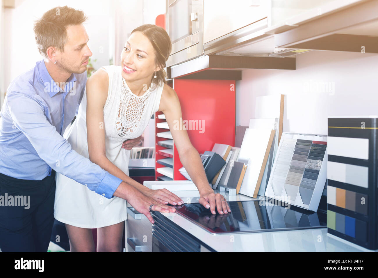family couple looking at modern kitchen tabletop in furniture