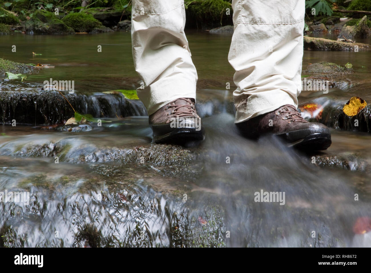 Hiker in Boots Standing in a River - Stock Image