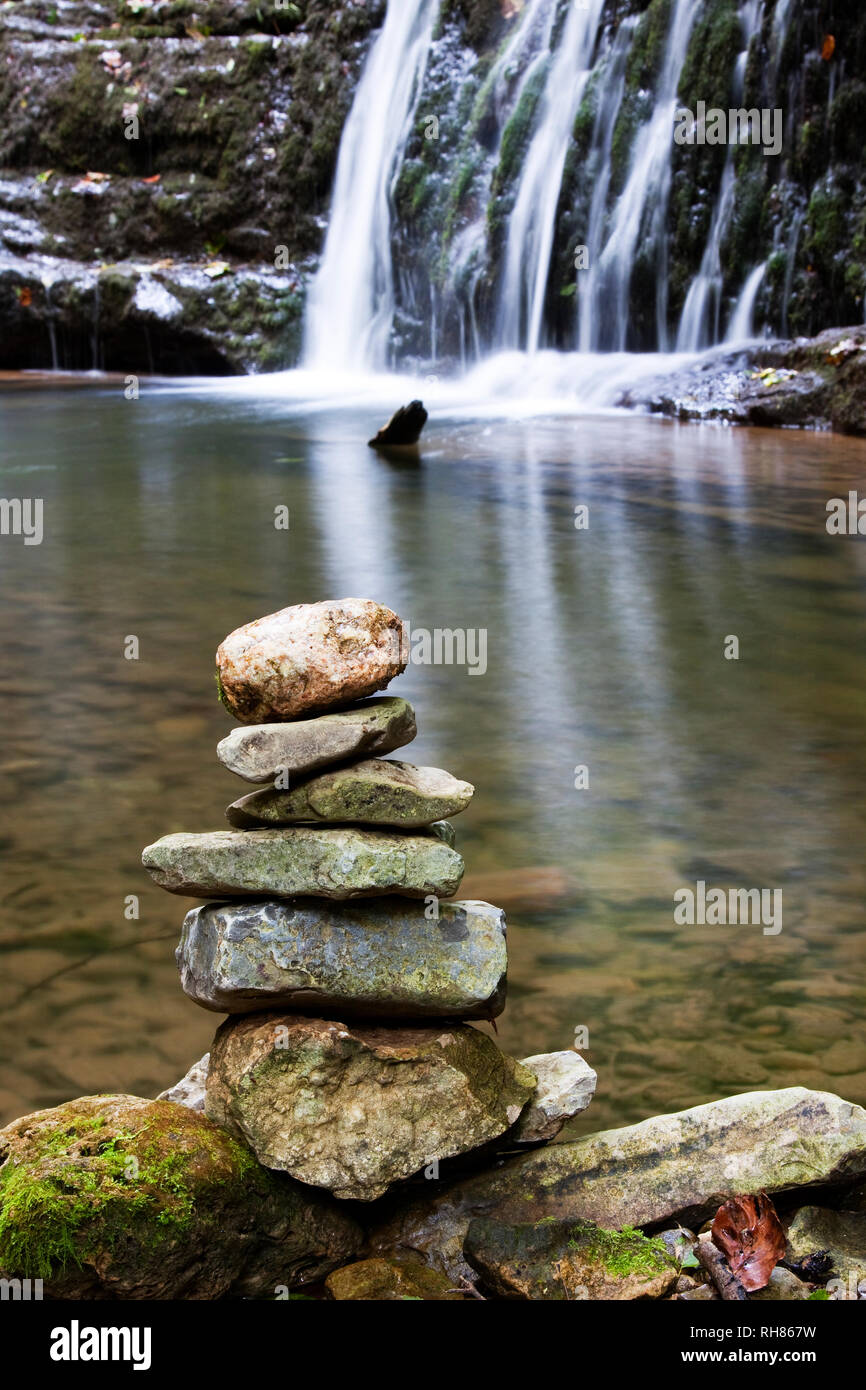 Balanced stones on a waterfall - Stock Image