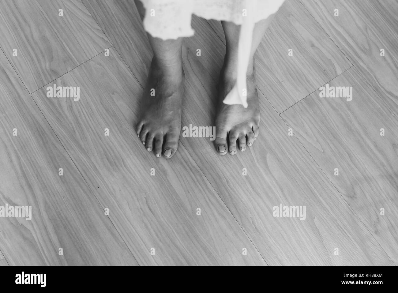 Black and white from above crop barefoot legs of lady in white wear standing on floor - Stock Image
