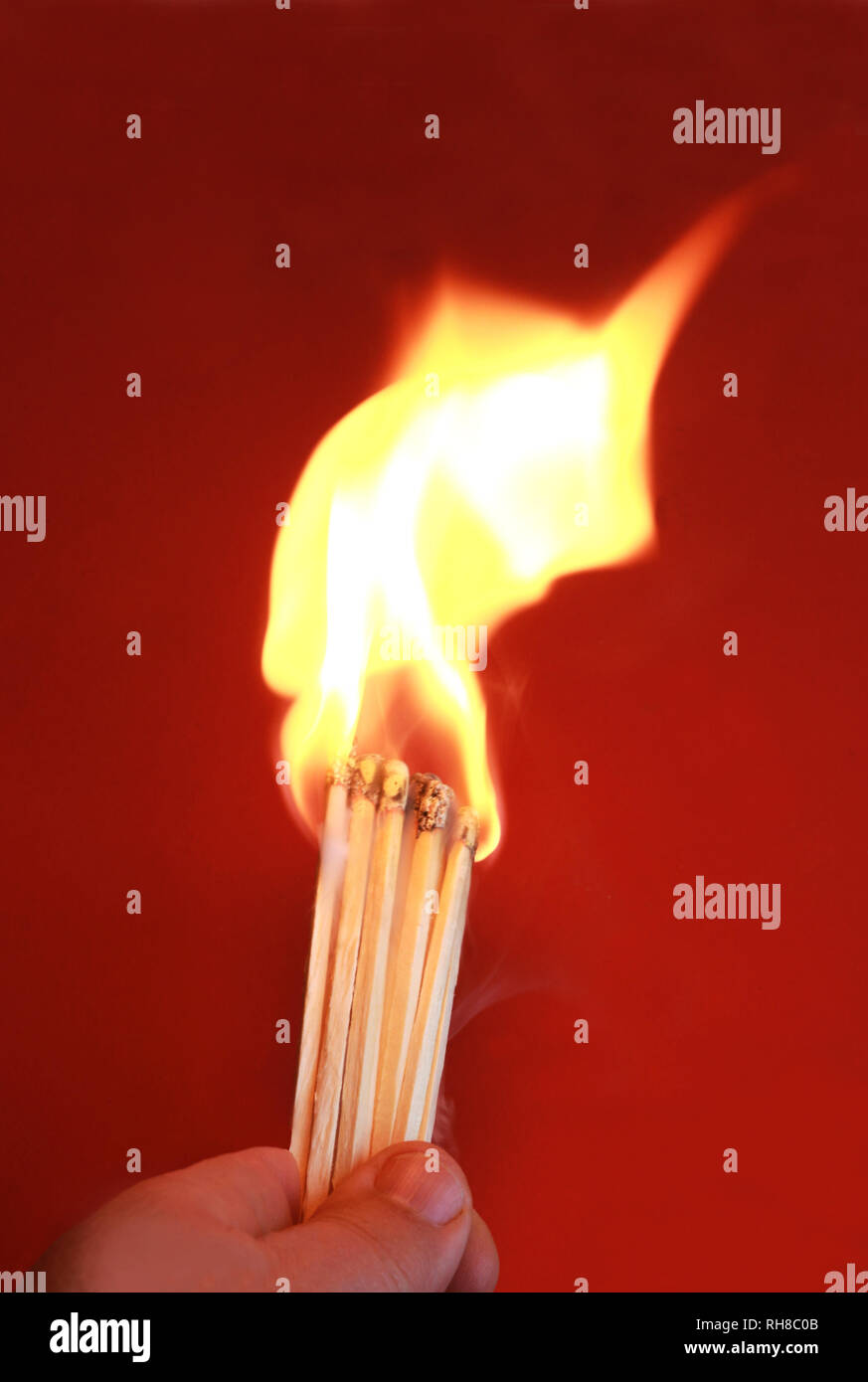 playing with fire, hand holding large matchsticks just inflamed, high flame - Stock Image