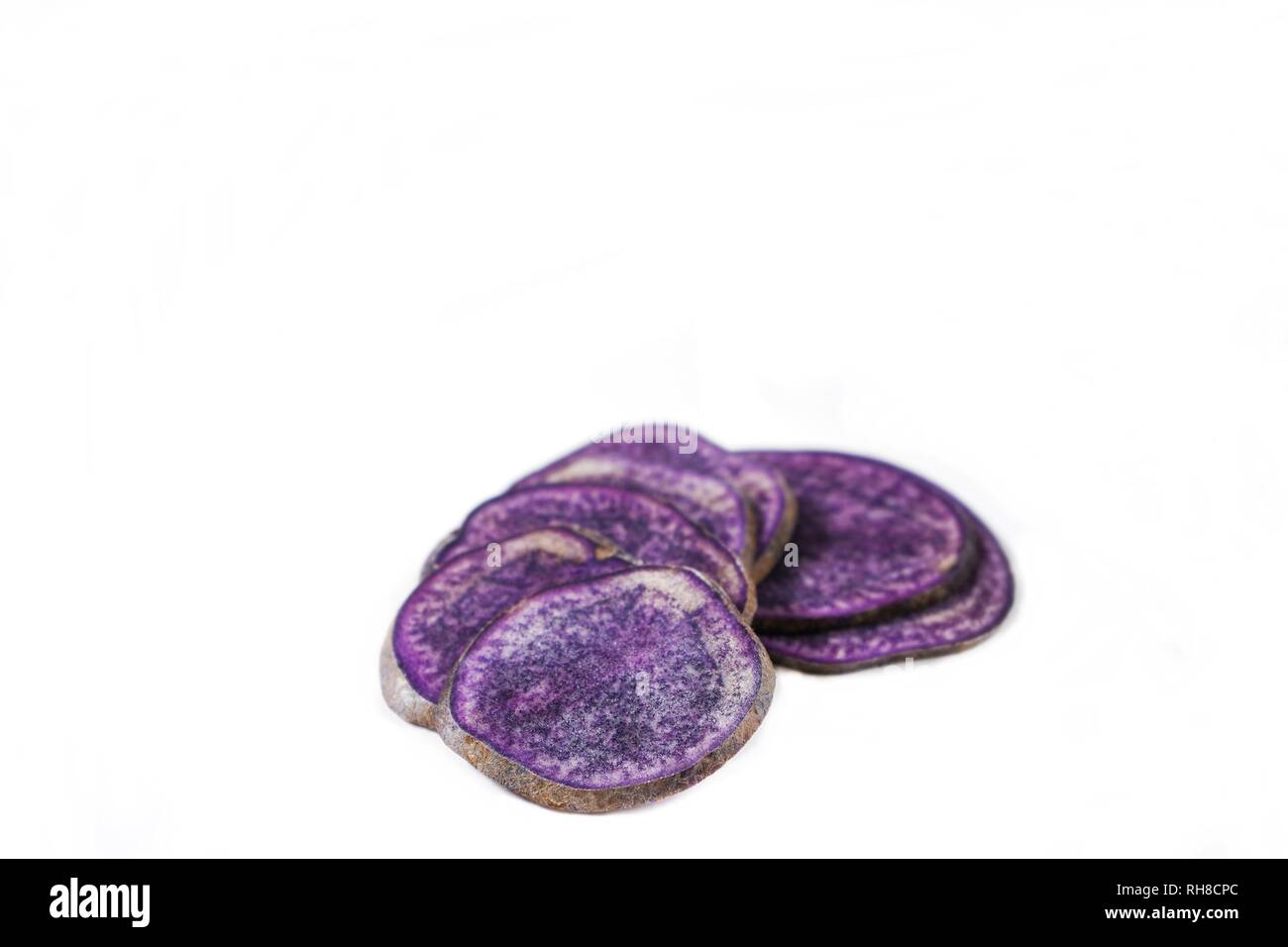 Purple Potatoes slices isolated on white, selective focus - Stock Image