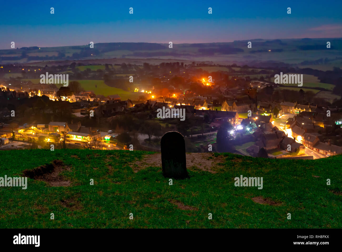 Nightime photograph overlooking Corfe village from nearby hilltop with waymarker stone. Corfe village, Dorset, England - Stock Image