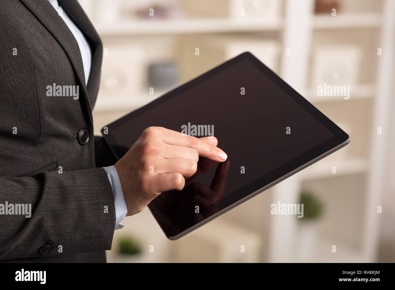 Business woman below chest using tablet in a homey environment  - Stock Image