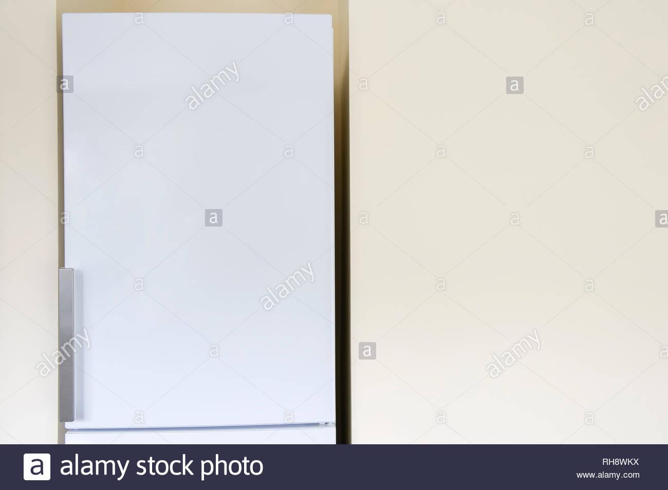 Fridge next to blank kitchen wall - Stock Image