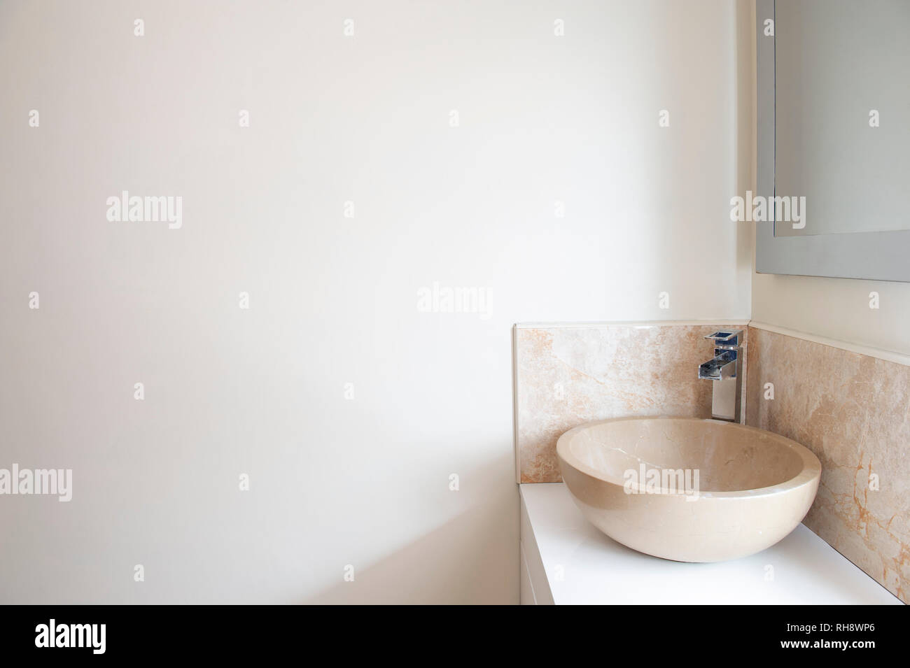 A granite wash basin (sink) on a white bathroom worktop in front of blank off white wall. - Stock Image
