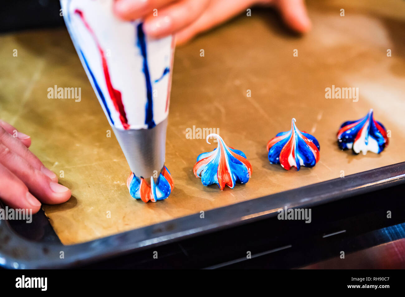 Close up baking pan with small meringue cakes made with pastry bag - Stock Image