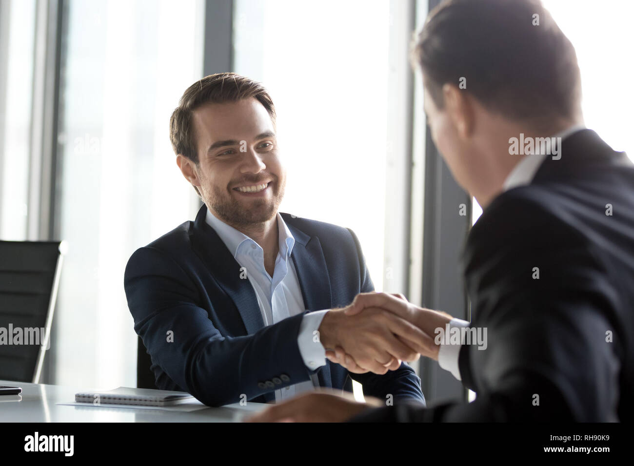 Happy successful businessmen shake hands after group negotiations, gratitude handshake - Stock Image