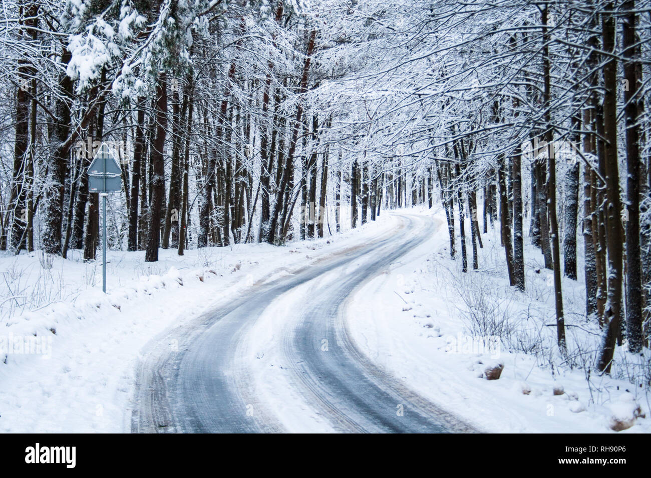 Slippery icy road through the forest with trees and snow on both sides - Stock Image