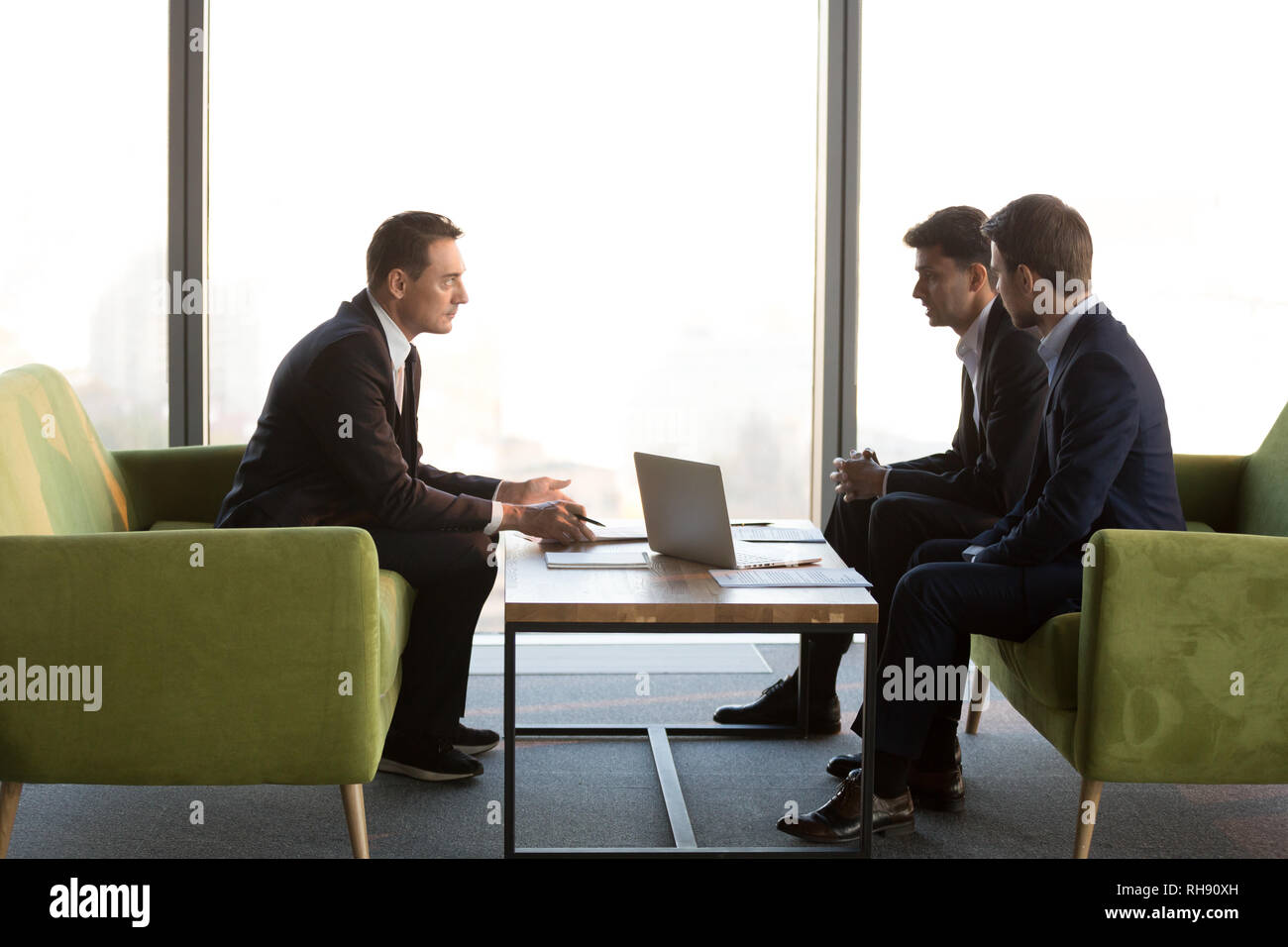 Diverse serious businessmen discuss new international project meeting investment adviser - Stock Image