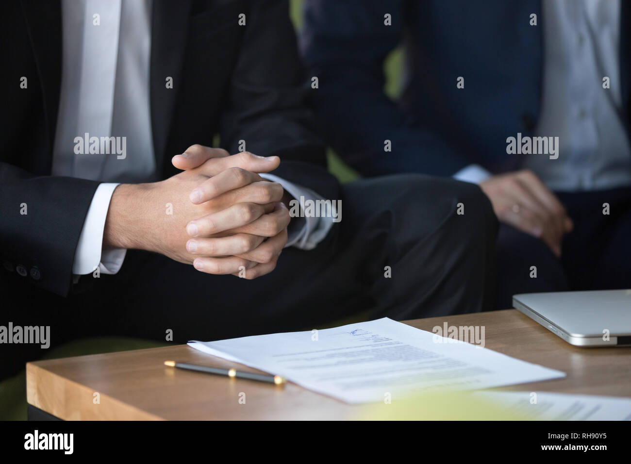 Clasped hands clenched together, businessman at negotiations focused on listening - Stock Image