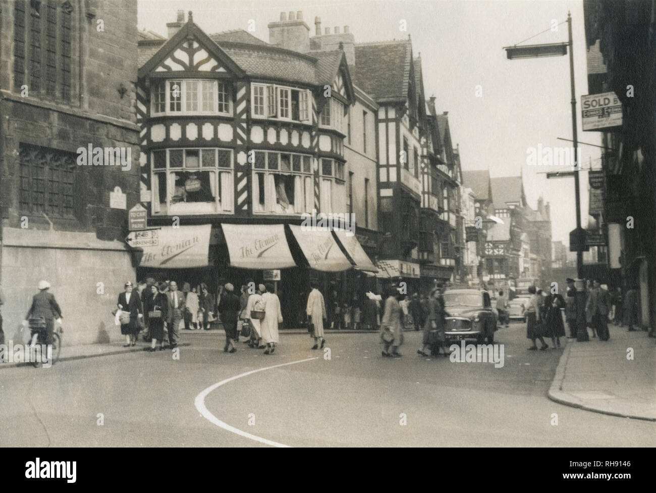 Antique c1950 photograph, The Etonian clothiers at 3b Eastgate St, Chester, England, UK. The photograph looks up Eastgate St from the Chester Cross, at the intersection with Northgate St (left) and Bridge St (right). SOURCE: ORIGINAL PHOTOGRAPH. Stock Photo