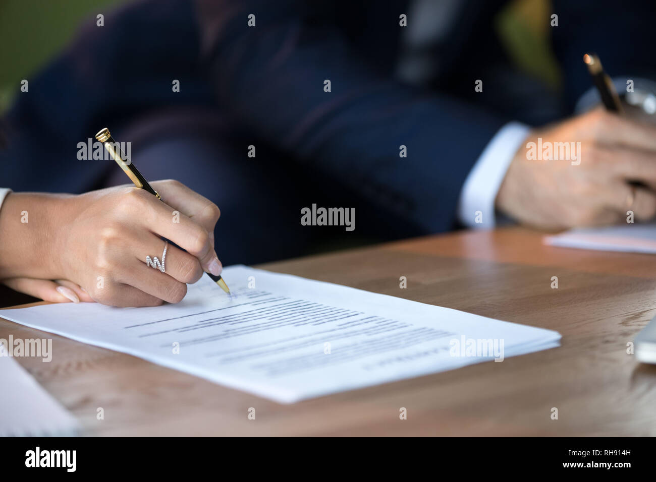 Close up view of woman and man signing document contract Stock Photo