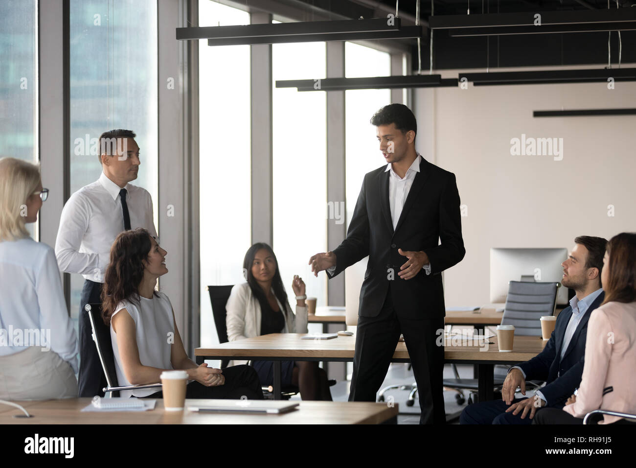 Arabic team leader talking to diverse business people at meeting - Stock Image