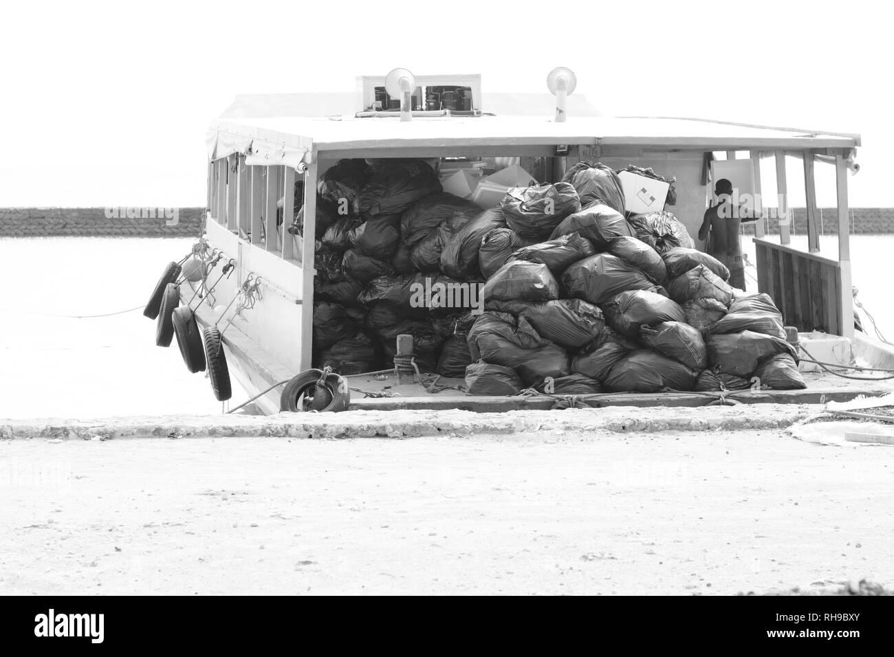 Ari Atoll, Maldives - 24 December 2018: A maldivian sailor is carrying trash bags with his boat - Stock Image