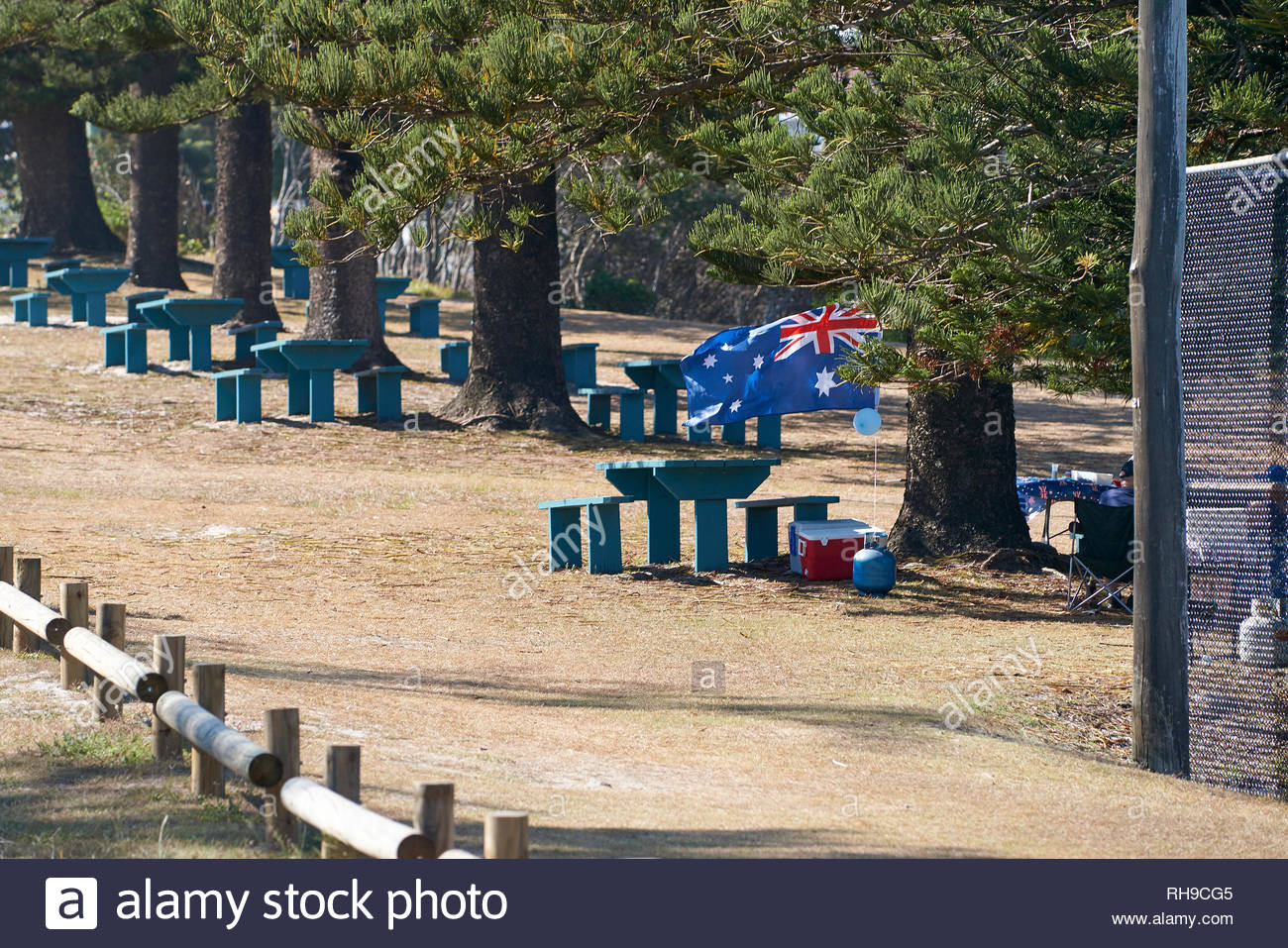 An Aussie flag flies in the breeze at a beachside barbecue...picnic tables and pines...on Australia Day - or Invasion Day - in Yamba, NSW, Australia. - Stock Image