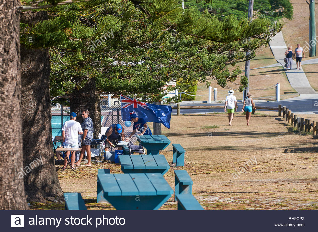 A barbecue near the beach, with passers-by and picnic tables and an Aussie flag; on Australia Day - or Invasion Day - in Yamba, NSW, Australia. - Stock Image