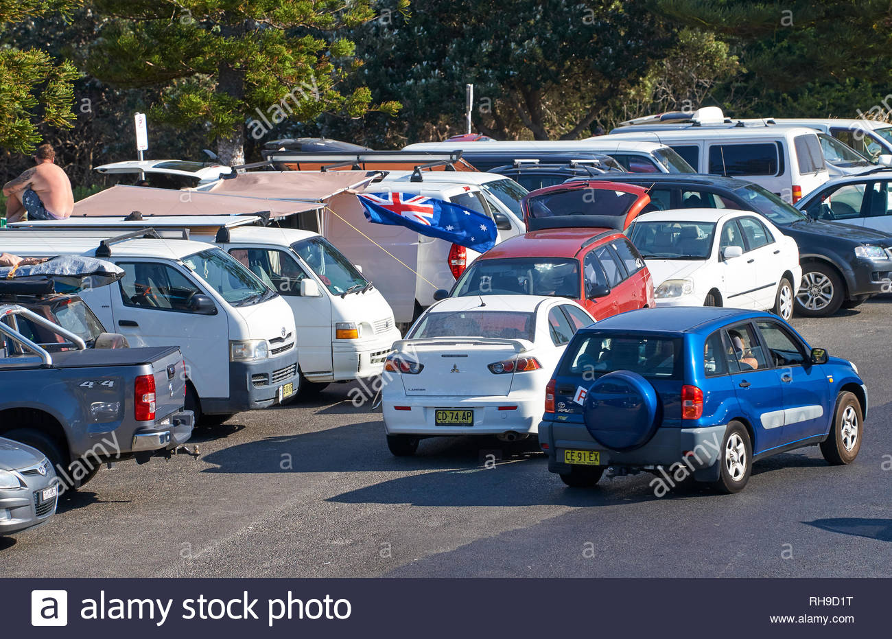 Lots of cars parked together - people gathering - above the beach to celebrate colonisation; on Australia Day - Invasion Day - Yamba, NSW, Australia. - Stock Image