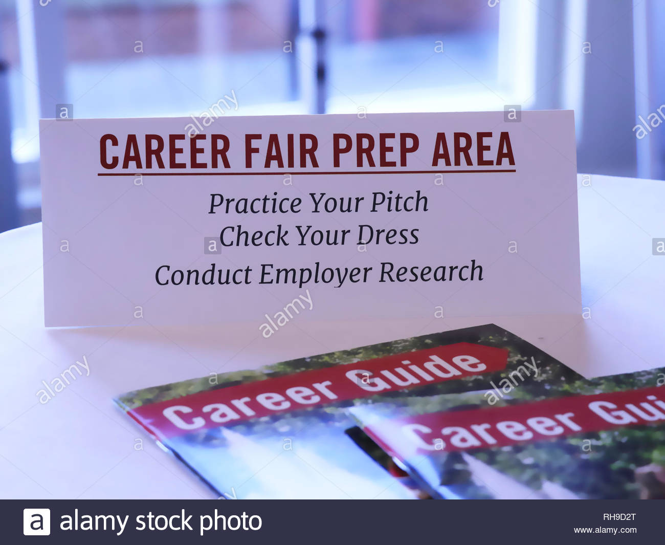 table tent and generic career guide magazines on a table outside a college career fair - preparation area for students before they enter the main hall - Stock Image