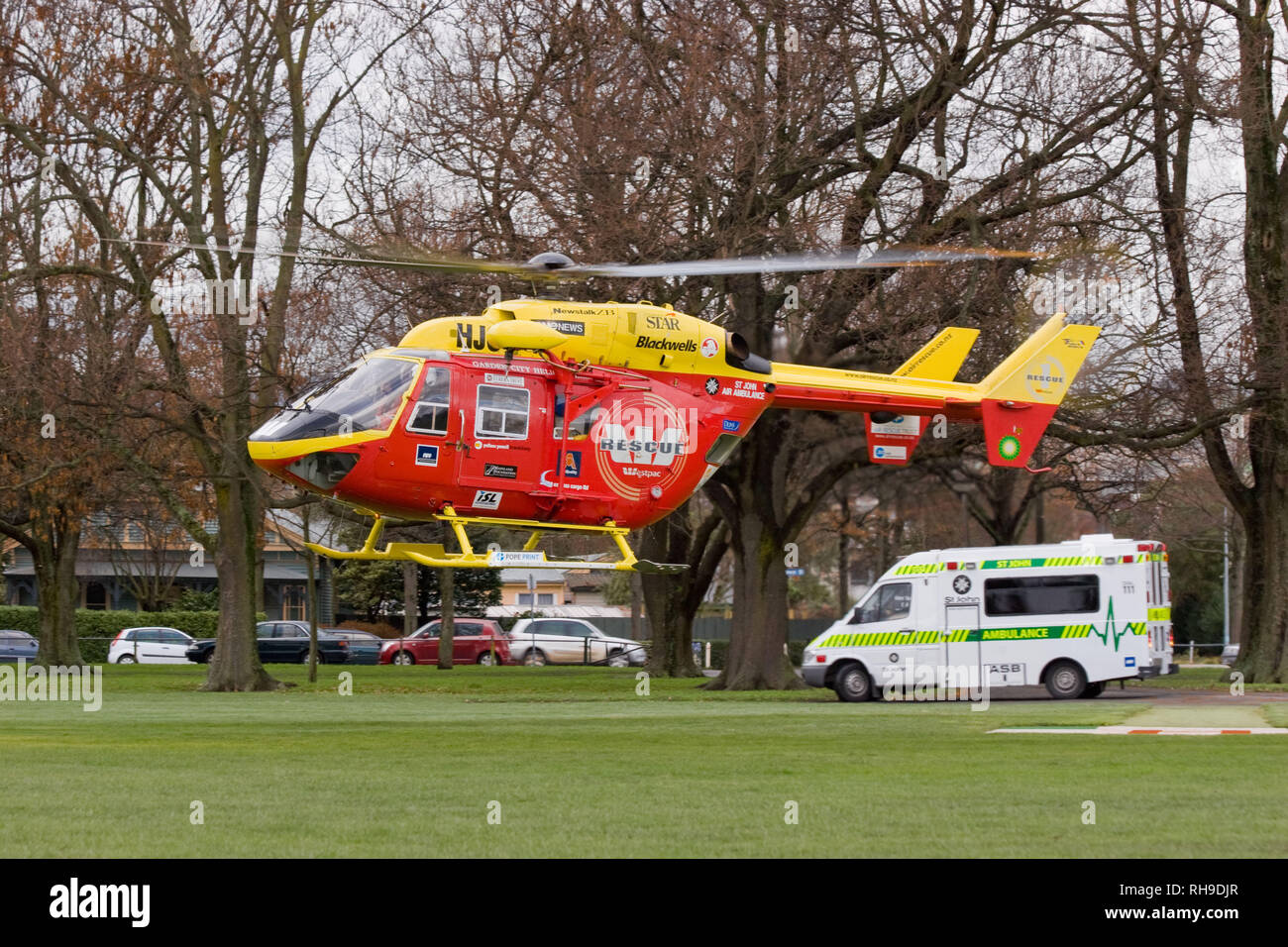 An MBB/Kawasaki BK 117 rescue helicopter meets a St John's ambulance in a local park to transfer a patient to Christchurch Hospital, New Zealand Stock Photo