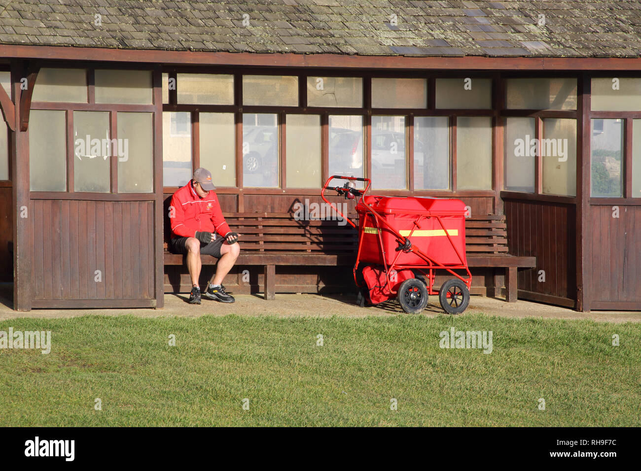 postman taking a break from his morning delivery round in hampshire england - Stock Image