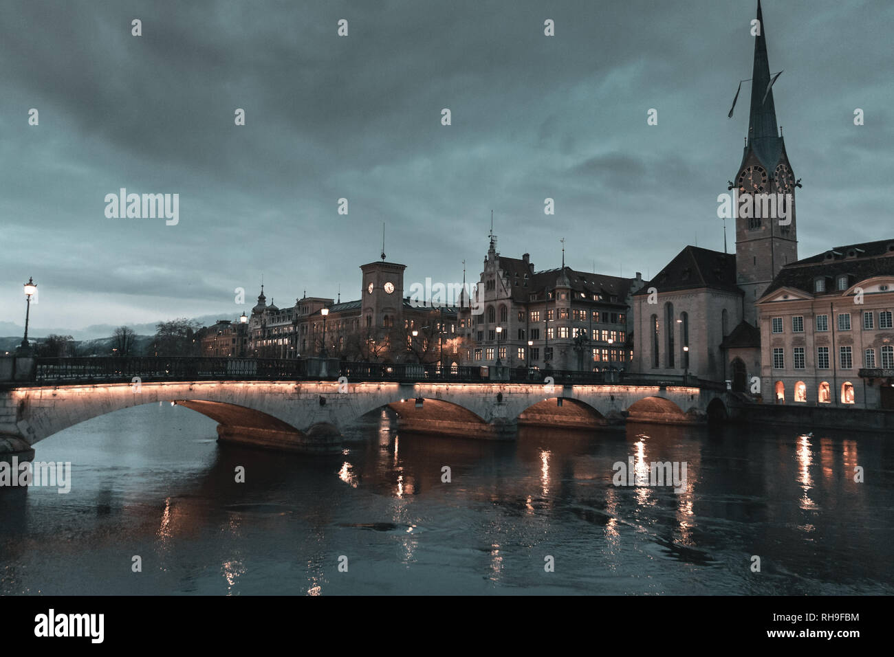 view of the old town of Zurich on Limmat river with Fraumünster church in the evening dawn - Stock Image