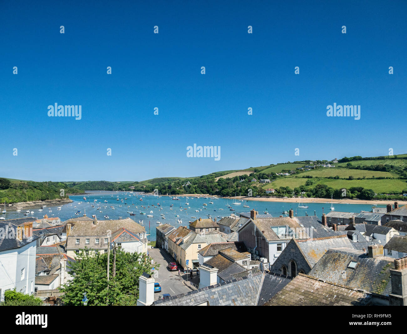3 June 2016: Salcombe, Devon UK - The Kingsbridge Estuary and roof tops of Salcombe on a warm and sunny spring day with clear blue sky. - Stock Image