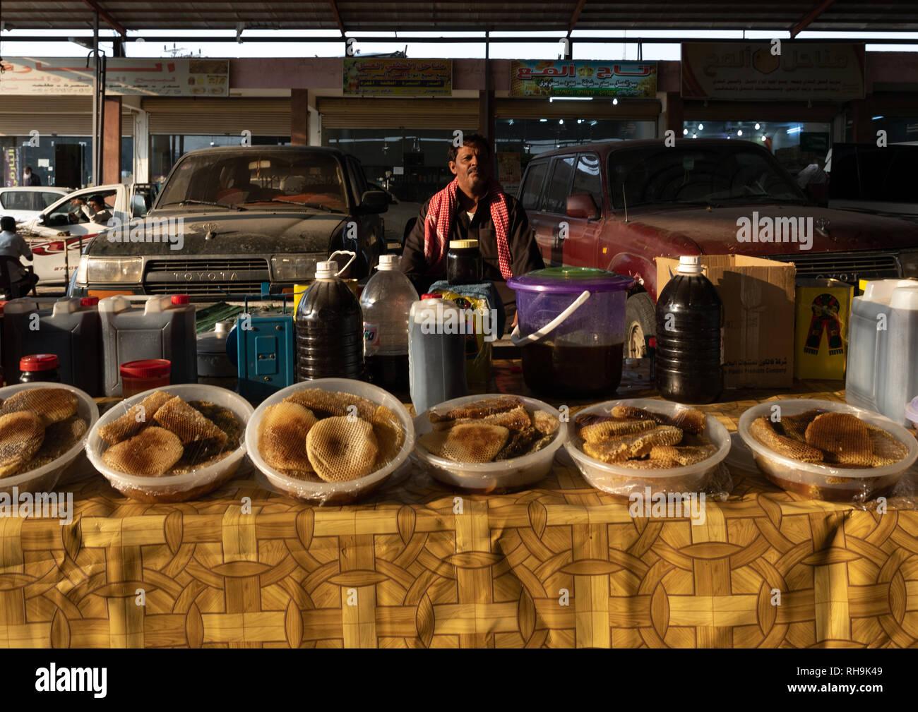 Saudi man selling honey and honeycombs on a market, Asir