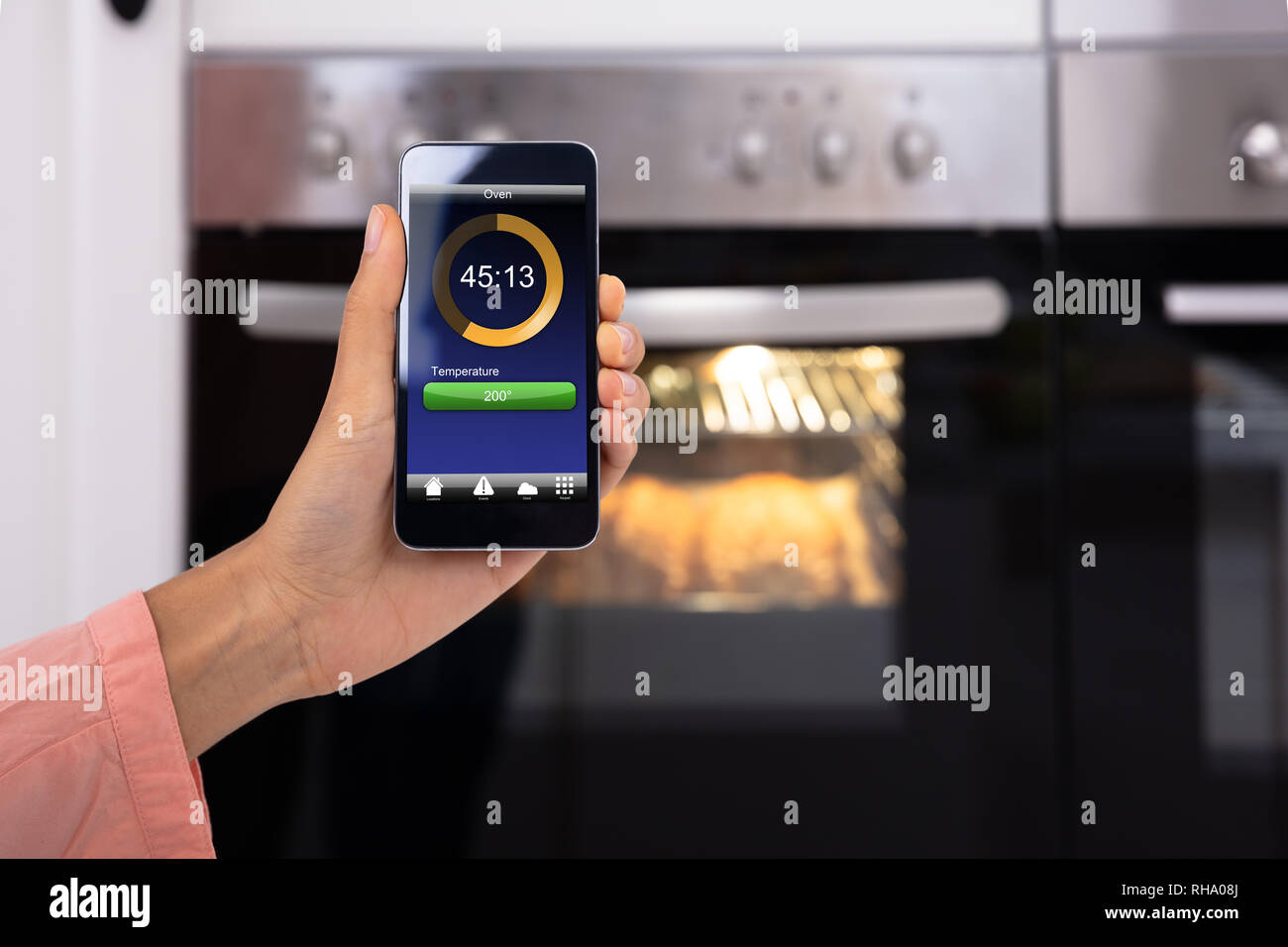 Close-up Of Woman's Hand Operating An Oven Application With Mobile Phone App - Stock Image