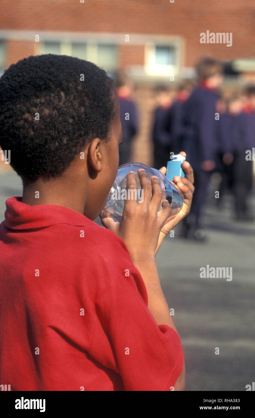 asthmatic black boy using ventolin inhaler attached to spacer in school playground - Stock Image