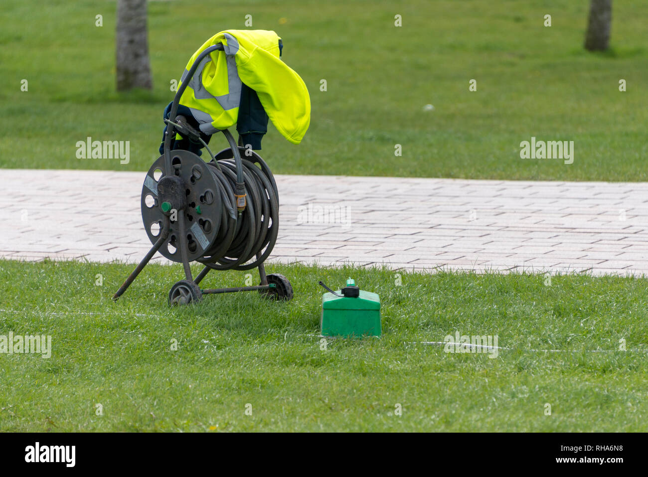 abandoned hose pipe reel and yellow vest with green fuel cannister Stock Photo
