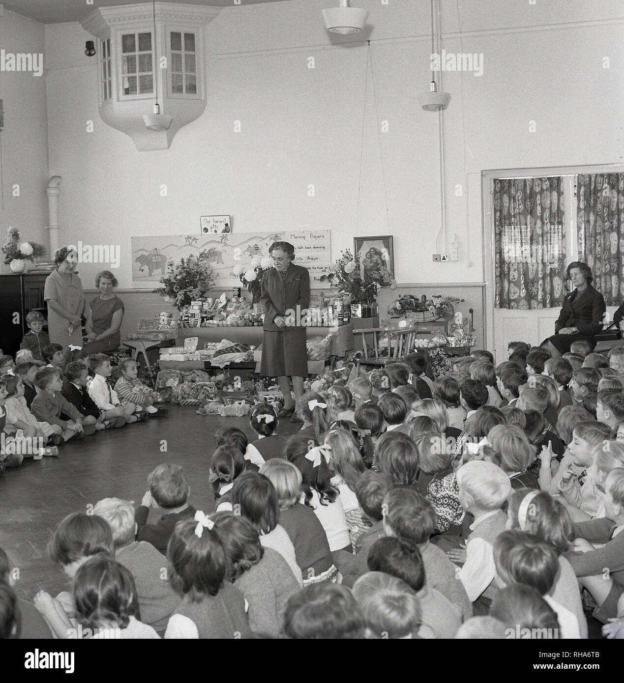 1964, primary school assembly, school children sitting together on the floor in a school hall to celebrate the harvest, when the farmers gather the crops from the fields, England, UK. The tradition dates back to pagan time, with the name deriving from the old English 'Haerfest', meaning 'Autumn'. - Stock Image