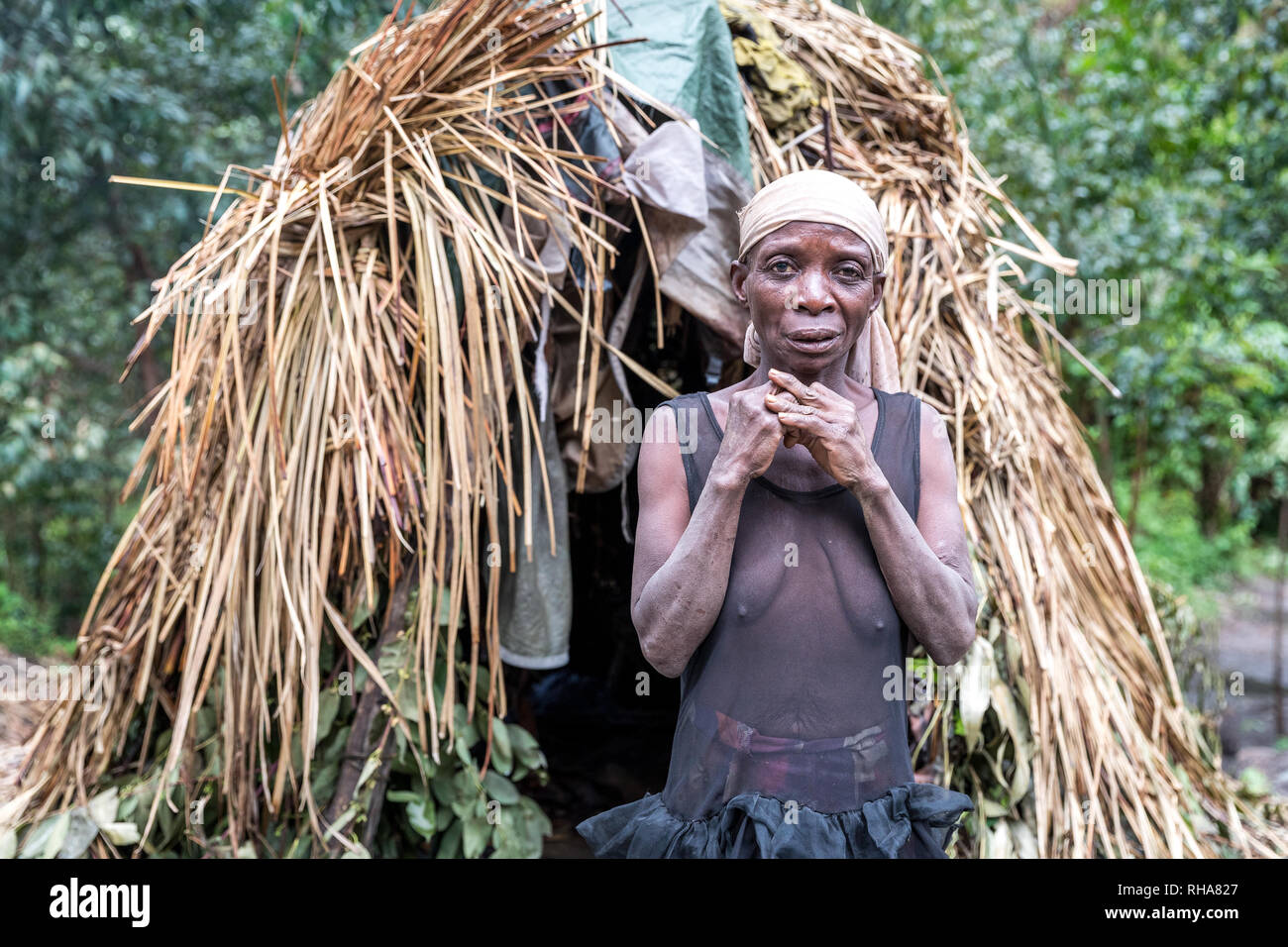 Portrait of pygmy tribeswoman standing in front of primitive hut, Uganda - Stock Image