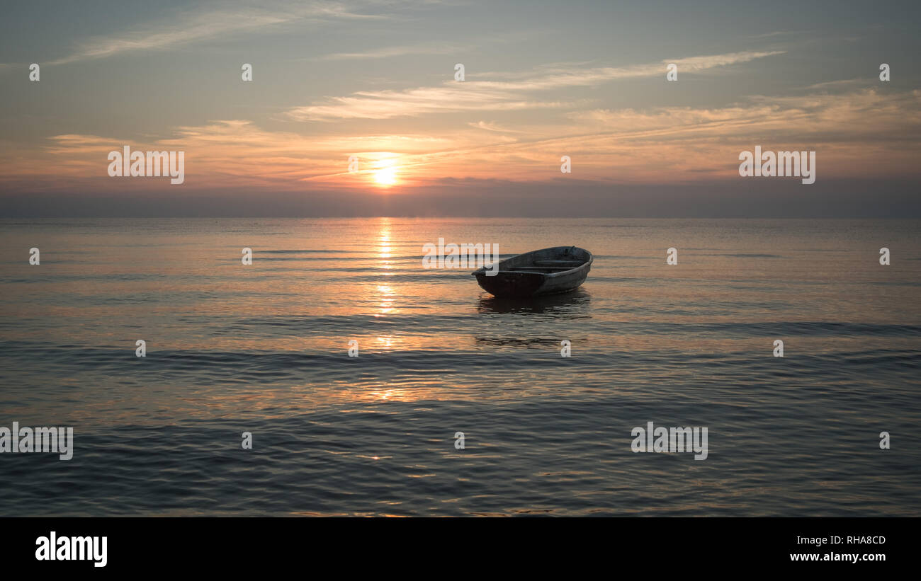 An empty boat surrounded by tiny waves of Baltic sea in warm light of distant rising sun on a quiet still morning. - Stock Image