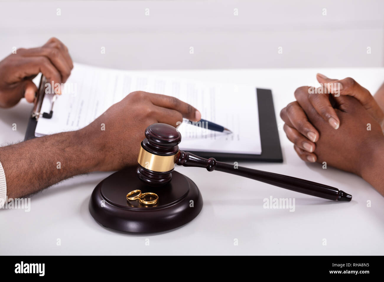 Close-up Of A Judge Explaining Contract To His Client With Gavel And Golden Rings Stock Photo