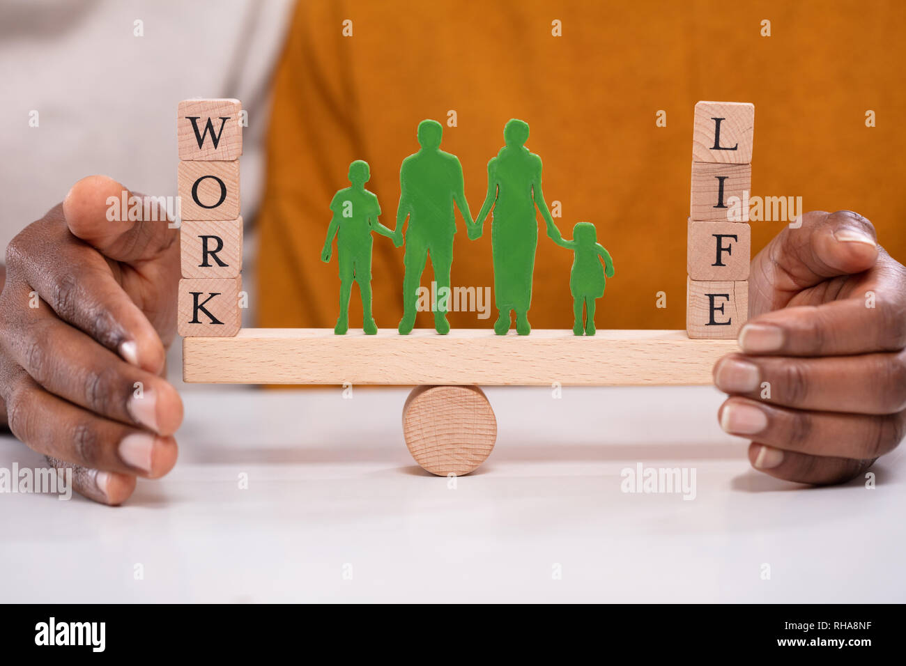 Person Protecting Work And Life Balance With Family Figures Standing Between Them On Seesaw - Stock Image