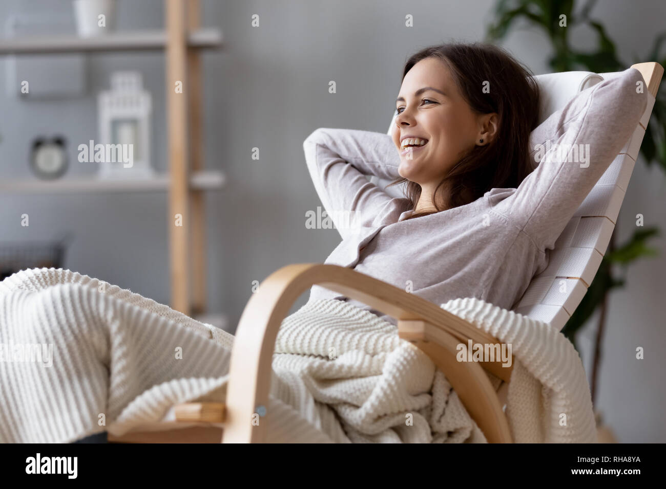 Happy millennial woman laughing resting on comfortable wooden rocking chair - Stock Image