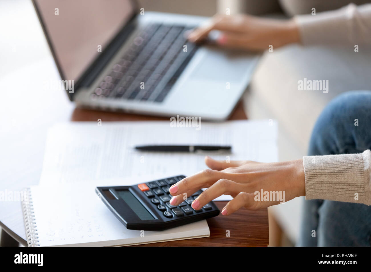 Businesswoman using calculator and laptop for budget cost management, closeup - Stock Image