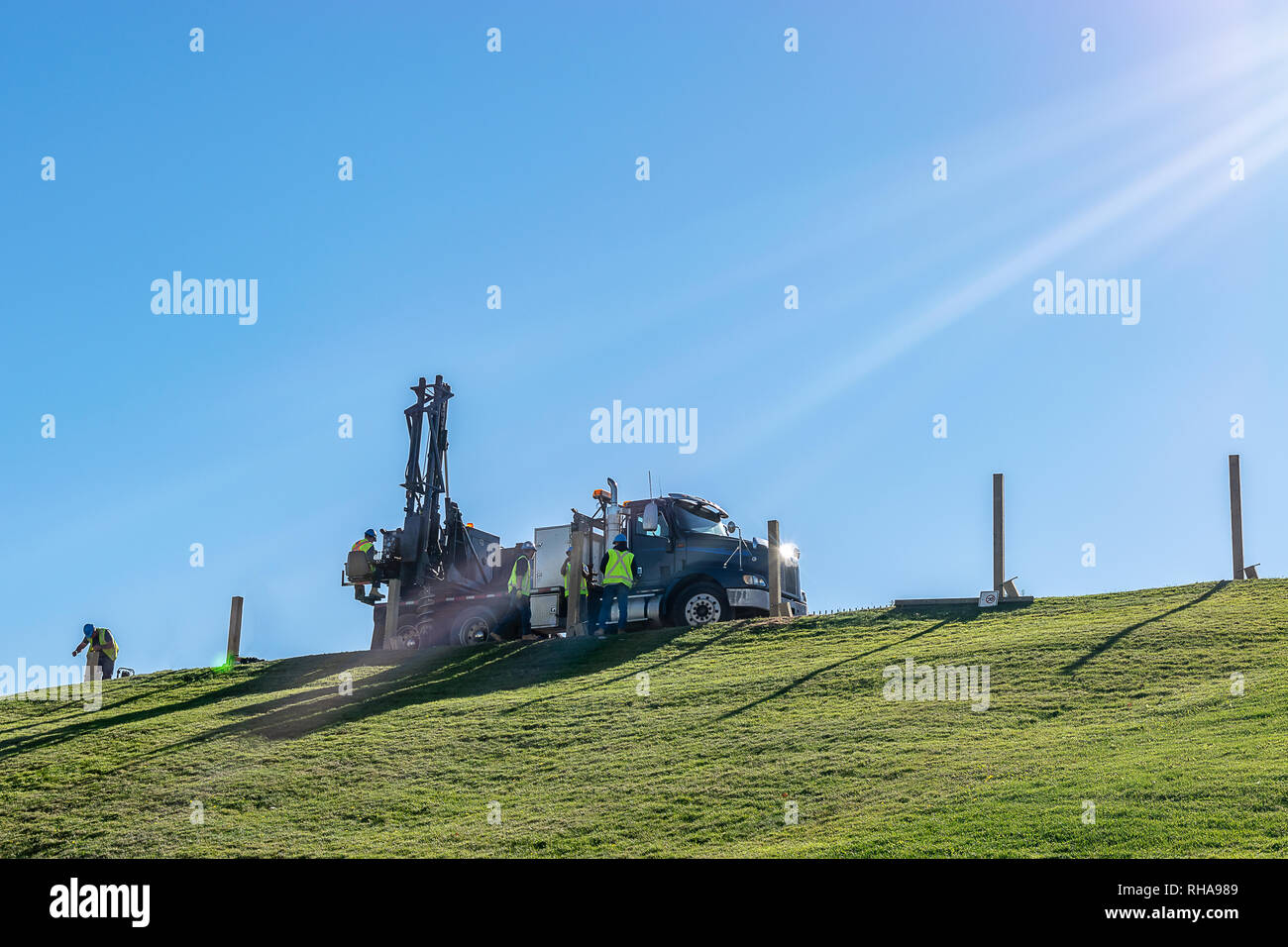 Caucasian male Engineers working and operating a hydraulic telescopic truck mounted auger crane drill rig on a hill on a sunny day. - Stock Image