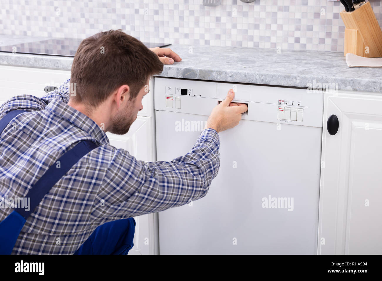 Young Serviceman Pressing Button Of Dishwasher In Kitchen - Stock Image