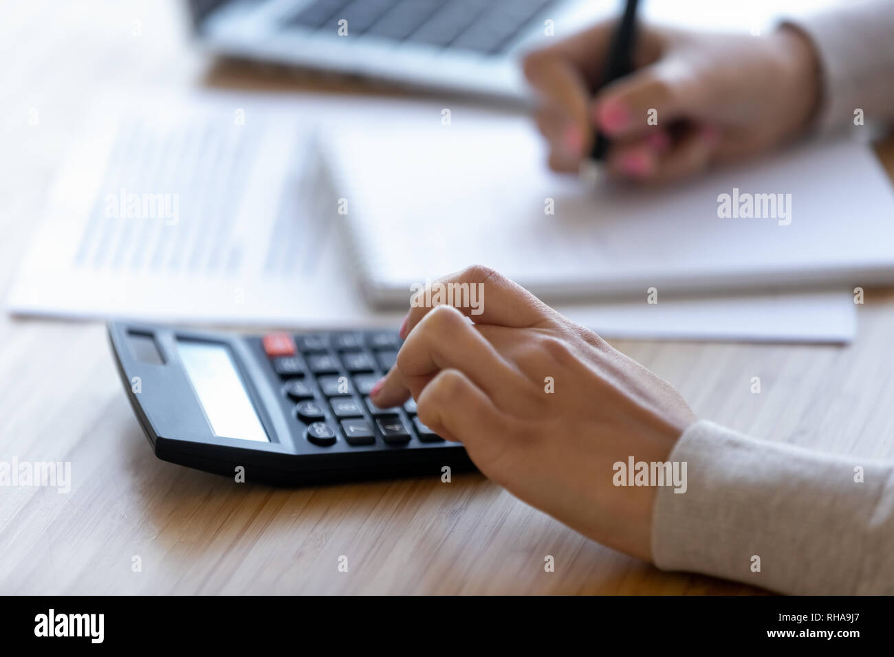 Female professional using calculator for business financial accounting, close up - Stock Image