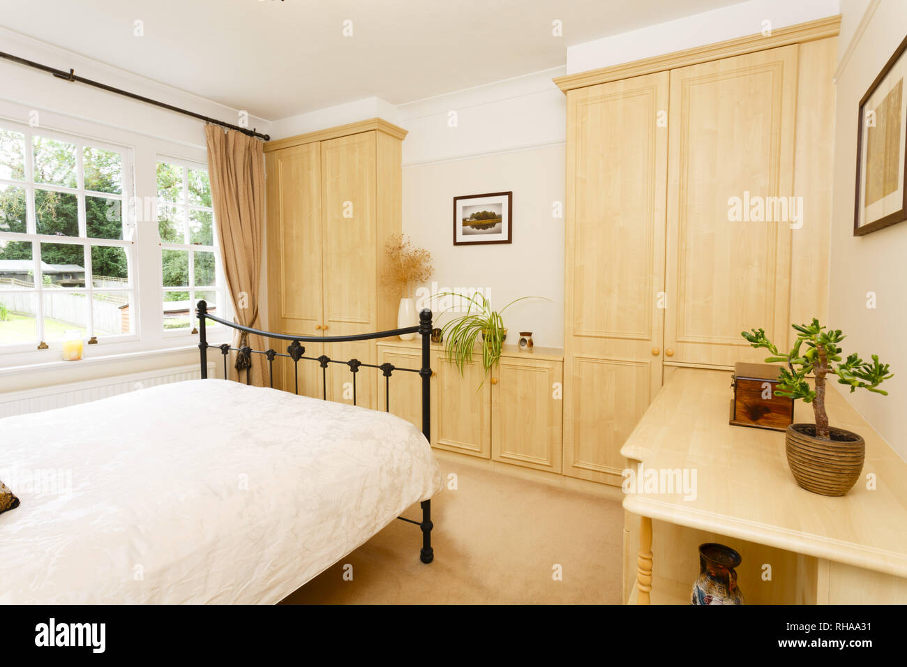 Modern bedroom with neutral colour scheme, cast iron bed and fitted wardrobes - Stock Image