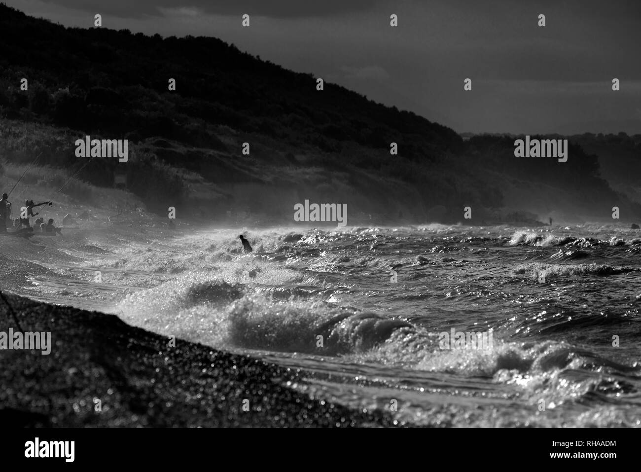 People swimming in the rough sea - Stock Image