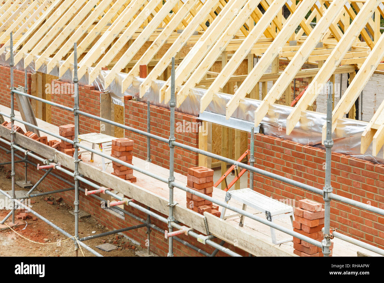 Construction site in UK with a house built from brick and timber, featuring brickwork, roof trusses and scaffolding - Stock Image