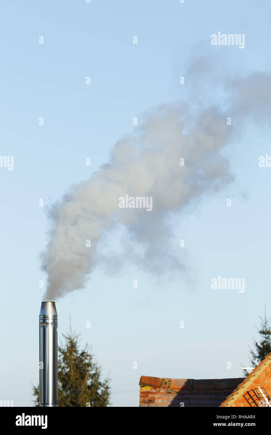 Domestic biomass chimney emitting smoke and pollution into the atmosphere - Stock Image