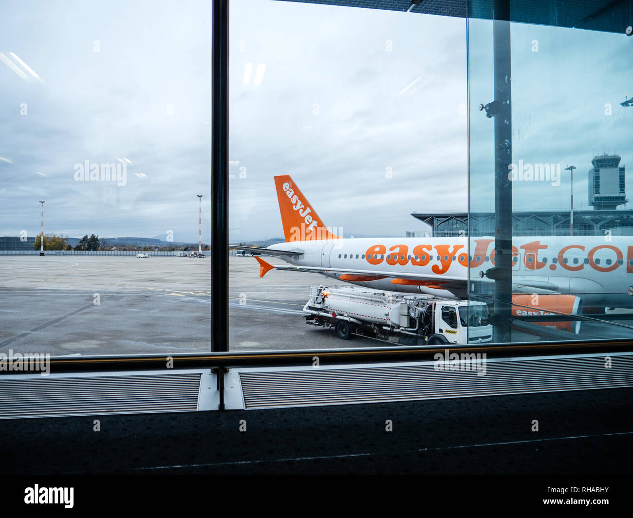 Basel, Switzerland - 11 Nov 2018: Airbus Boeing operated by EasyJet airlines on tarmac of Basel Mulhouse International Airport view from the interior of the Airport Terminal - Stock Image