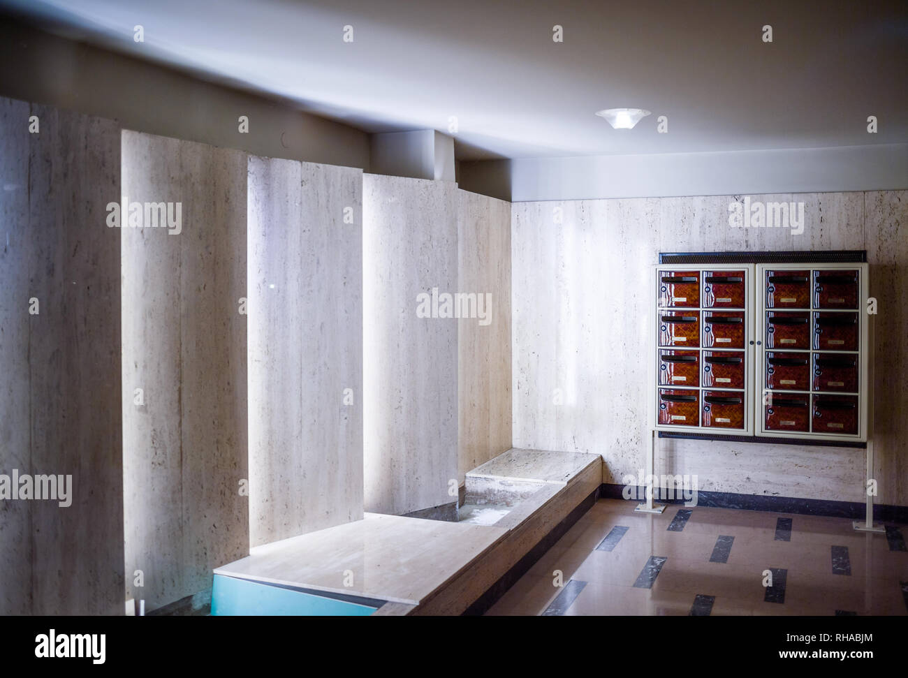 Entrance to modern vintage apartment building foyer lobby entrance with multiple postal boxes architectural illumination - Stock Image