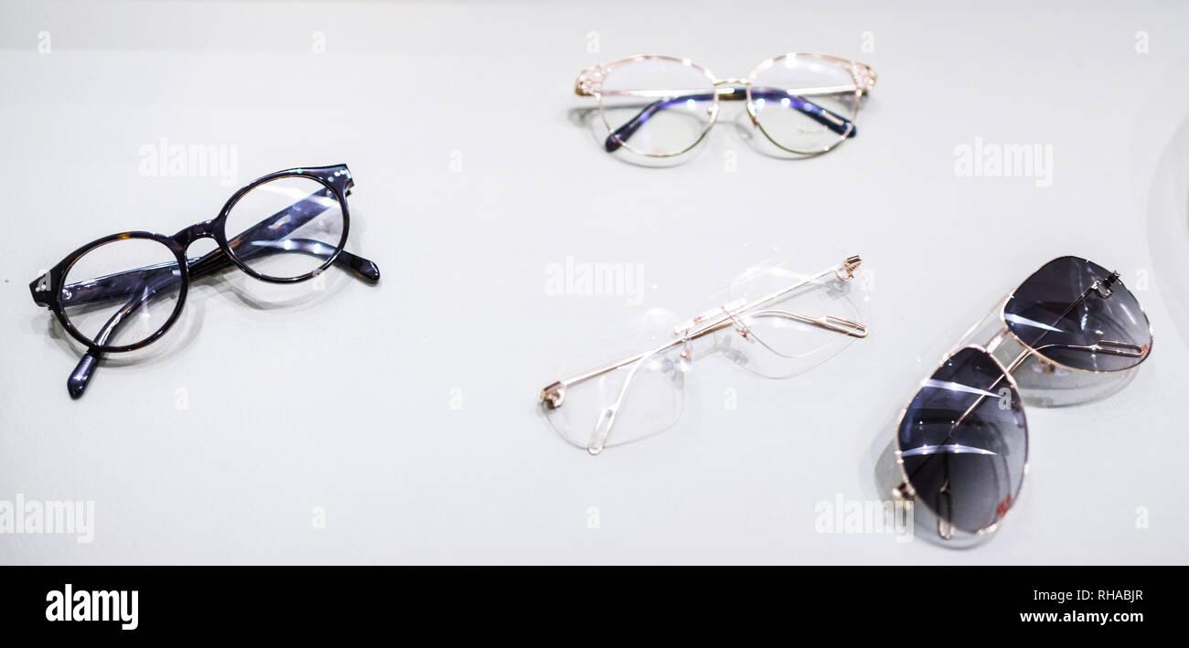 Multiple luxury golden and plastic eyewear frames at optometrist eyewear cabinet - Stock Image
