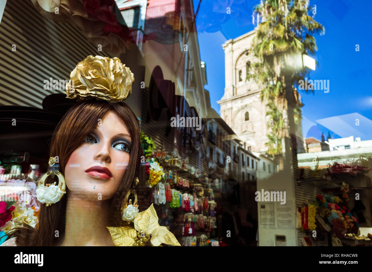 Granada, Andalusia, Spain : Window display with female mannequin in Rocio Flamenco fashion and reflections of the cathedral and Granada historic cente - Stock Image